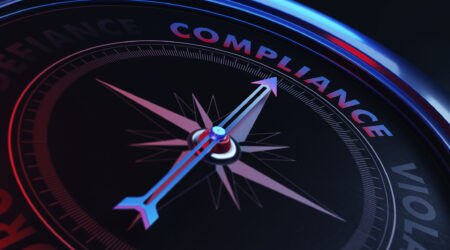 Arrow of a compass is pointing compliance text on the compass. Arrow, compliance text and the frame of compass are metallic blue in color. Red light illuminating compass is creating a sense of tension. Black backgound. Horizontal composition with copy space. Compliance concept.
